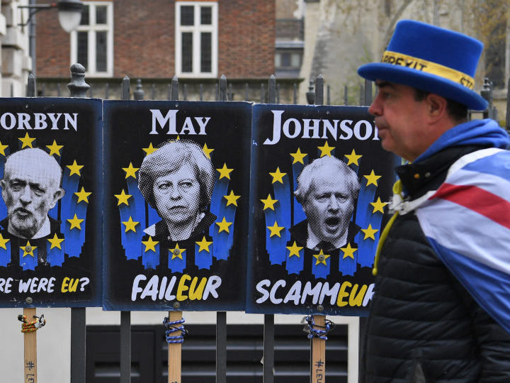 epa07480107 A Pro-EU campaigner walks past posters mocking British politicians in London, Britain, 02 April 2019. A 'no-deal' Brexit is more likely by the day, EU negotiator Michel Barnier has said after MP's were unable to find an alternative solution to Prime Minister Theresa May's deal.  EPA-EFE/ANDY RAIN