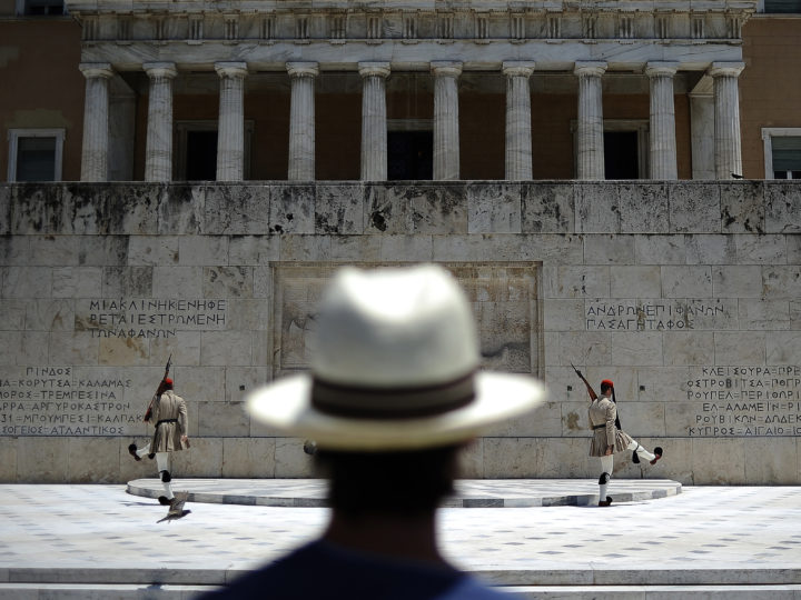 epaselect epa04828096 A tourist is watching the presidential guard in front of the Greek Parliament in central Athens, Greece, 02 July 2015. Greek Prime Minister Tsipras remained steadfast in his controversial plan to hold a referendum on the bailout demands of creditors, as eurozone finance ministers discussed a request from Athens for new financial aid. During the televized address to the nation on 01 July 2015 Tsipras said that anyone equating a no-vote with a return to the drachma is 'telling lies,' and repeated his call for people to vote against the measures.  EPA/FOTIS PLEGAS G.